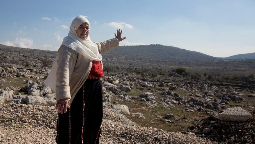 In this Monday, Jan. 1, 2017 photo, Maryam Abdel-Kareem, 82-year-old Palestinian, points to land held by the Jewish settlement of Amona, an unauthorized outpost in the West Bank, near the village of Silwad, east of the West Bank city Ramallah. Abdel-Kareem and a group of other Palestinian landowners is set to reclaim the property they watched stripped from them two decades ago, hoping to finally put to rest a bitter, years-long battle that thrust them into a protracted legal saga and a political crisis that threatened to tear apart Israel's governing coalition. (AP Photo/ Majdi Mohammed )