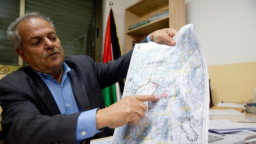 In this Monday, Jan. 1, 2017 photo, mayor of the Palestinian village of Silwad Abdulrahman Saleh shows on a map land held by the Jewish settlement of Amona, an unauthorized outpost in the West Bank, near the village of Silwad, east of the West Bank city Ramallah. A group of Palestinian landowners is set to reclaim the property they watched stripped from them two decades ago, hoping to finally put to rest a bitter, years-long battle that thrust them into a protracted legal saga and a political crisis that threatened to tear apart Israel's governing coalition. (AP Photo/ Majdi Mohammed )