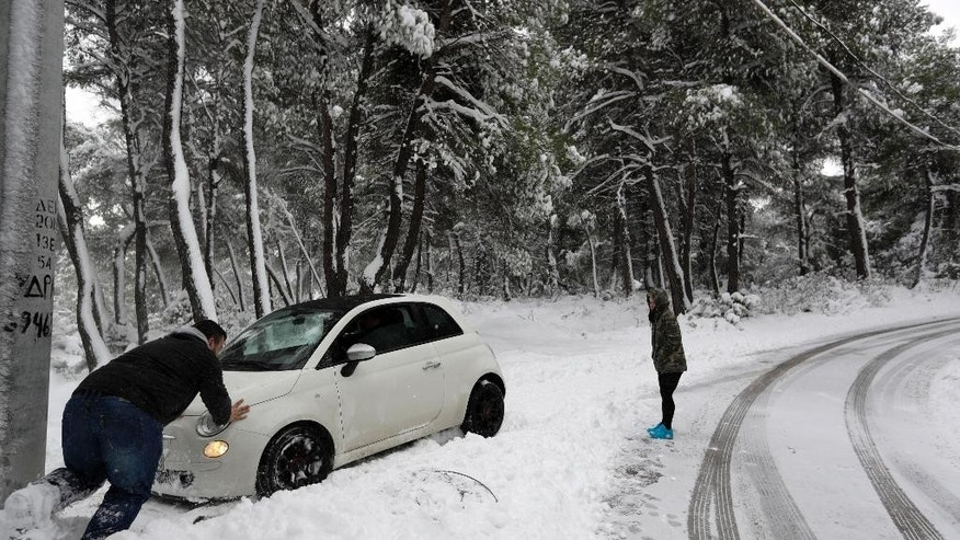 A man pushes a car from the snow after his driver lost control, in Malakasa about 29 kilometers (24 miles) north of Athens on Tuesday, Jan. 10, 2017. Snow closed schools in the capital, as added pressure on the government to speed up winter preparations for thousands of refugees living in camps around the country. (AP Photo/Thanassis Stavrakis)