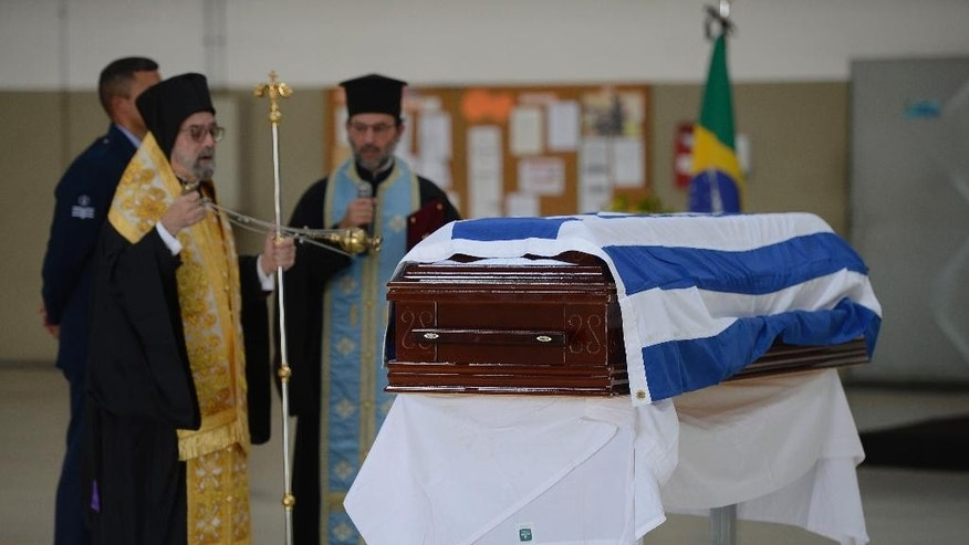 In this photo released by Agencia Brasil, a ceremony is held for Greece's late Ambassador to Brazil Kyriakos Amiridis before his remains are flown home from the airport in Rio de Janeiro, Brazil, Tuesday, Jan. 10, 2017. Amiridis went missing Dec. 26 in Nova Iguacu, a city near Rio de Janeiro where he had been vacationing with his wife. His charred body was found in a car three days later. Police say they believe he was killed by his wife's lover under her orders. (Tania Rego/Agencia Brasil via AP)