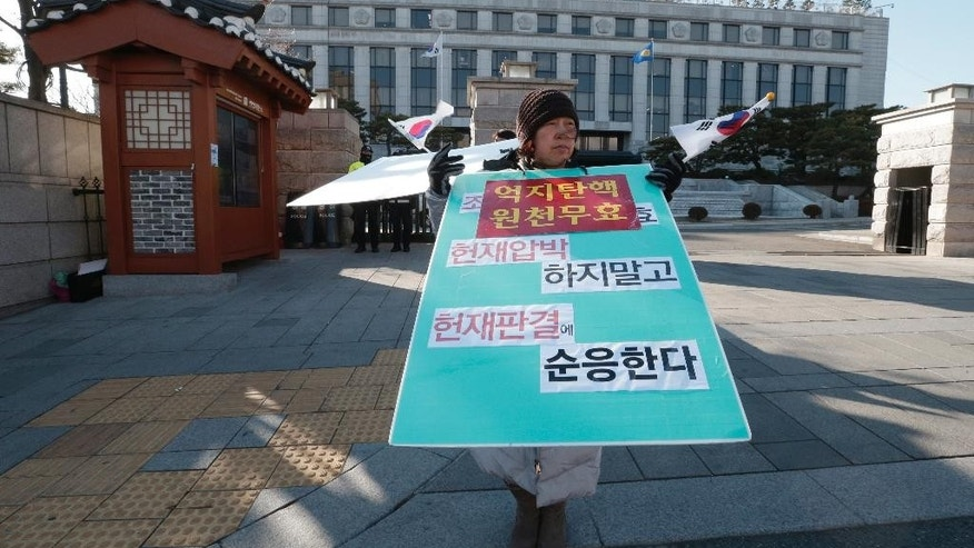 "A supporter of disgraced South Korean President Park Geun-hye stands to oppose her impeachment in front of the Constitutional Court in Seoul, South Korea, Tuesday, Jan. 10, 2017. Park's longtime friend at the center of a massive corruption scandal refused to testify at Park's impeachment trial on Tuesday. The sign held by the supporter reads: ""Nullity of impeachment."" (AP Photo/Ahn Young-joon)"
