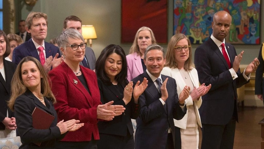 Minister of Foreign Affairs Chrystia Freeland, Minister of Labour Patty Hajdu, Minister of Status of Women Maryam Monsef, Minister of International Trade Francois-Philippe Champagne, Minister of Democratic Institutions Karina Gould and Minister of Immigration, Refugees and Citizenship Ahmed Hussen applaud before being sworn-in during a cabinet shuffle at Rideau Hall in Ottawa,  Tuesday, Jan. 10, 2017. (Adrian Wyld/The Canadian Press via AP)