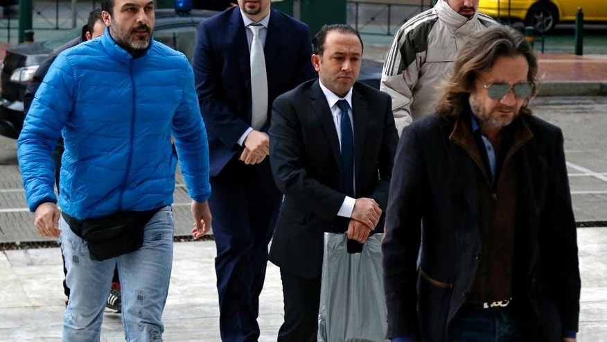 Two Turkish military officers wearing handcuffs, center, escorted by plain-clothed police officers arrive at the Supreme Court in Athens, on Wednesday, Jan. 11, 2017. A prosecutor at Greece's highest court recommended on Tuesday the court reject an extradition request for two other Turkish servicemen, who fled to Greece after a failed July military coup in their country. (Stelios Misinas/Eurokinissi via AP)