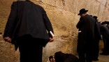 An Ultra-orthodox Jewish man sleeps as others pray during the mourning ritual of Tisha B'Av at the Western Wall, the holiest site where Jews can pray, in Jerusalem's Old City, Tuesday, Aug. 9, 2011. The Jewish holy day of Tisha B'Av, when Jews mourn the destruction of the biblical temples, is marked Tuesday. (AP Photo/Bernat Armangue)