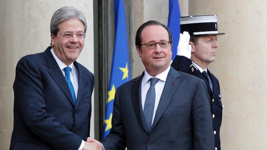 FILE - In this Jan. 10, 2016 file photo, French President Francois Hollande, right, welcomes Italian Premier Paolo Gentiloni before their talks at the Elysee Palace in Paris. According to reports Wednesday, Jan. 11, 2016, Gentiloni was hospitalized in Rome upon his return from Paris following a sudden indisposition and successfully underwent a minor angioplasty surgery.  (AP Photo/Christophe Ena, FILE)