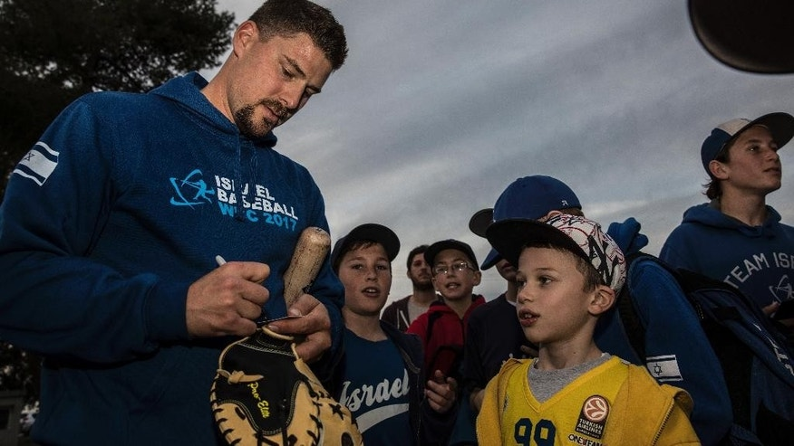 In this photo made on Thursday Jan, 5 2017, Ryan Lavarnway, an American professional baseball player, signs autographs to Israeli fans before the practice at the Baptist Village sport complex near Petah Tikva, Israel. Israel has just one proper baseball diamond, and most Israelis know next to nothing about the game. Yet the country has emerged as a potential spoiler in the upcoming World Baseball Classic thanks to quirky regulations that allow it to pack its squad with American pro players of Jewish descent. (AP Photo/Tsafrir Abayov)