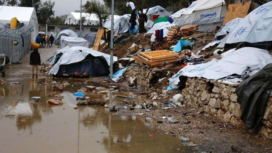 A refugee stands next to a pool of mud at Moria refugee camp on the eastern Greek island of Lesbos, Tuesday, Jan. 10, 2017. Officials said they planned to move some 250 people Tuesday, following strong criticism from aid agencies and medical associations that refugees had been left unprotected during the last heavy snowfall. (Petros Tsakmakis/InTime News via AP)
