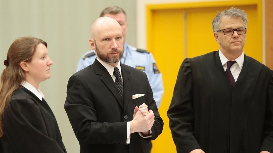 Anders Behring Breivik, center, arrives for his appeal case flanked by his defense lawyers Mona Danielsen, left, and Oystein Storrvik in Borgarting Court of Appeal at Telemark prison in Skien, Norway, Tuesday, Jan. 10, 2017. Norwegian mass murderer Anders Behring Breivik walked quietly into a courtroom at a high security prison Tuesday, making a neo-Nazi salute, as judges began reviewing a government appeal against a ruling that his solitary confinement was inhumane and violated human rights. (Lise Aaserud/NTB Scanpix via AP)