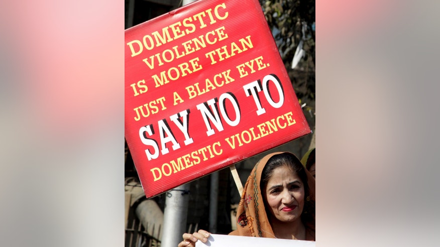 An activist rallies with others to condemn domestic violence, in Lahore, Pakistan, Wednesday, Jan. 11, 2017. Pakistan's chief justice is demanding a full police probe into allegations that a 10-year-old girl working as a maid was tortured by her employers, an influential judge and his wife. (AP Photo/K.M. Chaudary)