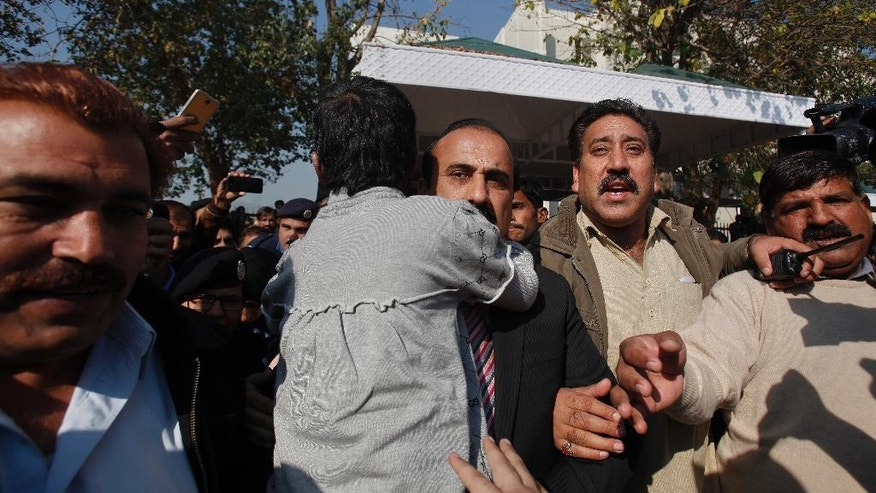 Pakistani plainclothes police officers make way for social worker Zamurd Khan, center, carrying a young girl, who worked as a maid and was allegedly tortured by her employers, following her appearance in Supreme Court in Islamabad, Pakistan, Wednesday, Jan. 11, 2017. Pakistan's chief justice is demanding a full police probe into allegations that the 10-year-old girl working as a maid was tortured by her employers, an influential judge and his wife. (AP Photo/Anjum Naveed)