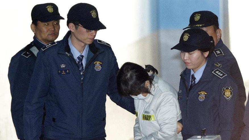 Choi Soon-sil, center, disgraced South Korean President Park Geun-hye's longtime friend at the center of a massive corruption scandal, arrives for her trial at the Seoul Central District Court in Seoul, South Korea, Wednesday, Jan. 11, 2017. Choi refused to testify at Park's impeachment trial on Tuesday, with lawmakers alleging that it was a stalling tactic. (AP Photo/Ahn Young-joon)