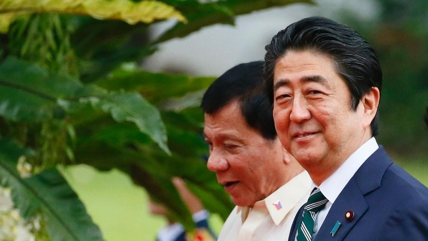 Japanese Prime Minister Shinzo Abe, right, and Philippine President Rodrigo Duterte walk together for their meeting at the Malacanang Palace grounds, Thursday, Jan. 12, 2017, in Manila, Philippines. Abe arrived Thursday for a two-day official visit that includes a visit to Duterte's hometown of Davao city in southern Philippines.(AP Photo/Bullit Marquez)
