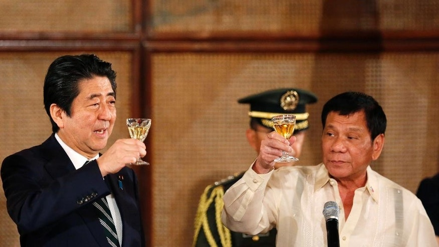 Japanese Prime Minister Shinzo Abe, left, and Philippine President Rodrigo Duterte toast during a state banquet at the Malacanang Palace Thursday, Jan. 12, 2017 in Manila, Philippines. Abe arrived Thursday for a two-day official visit that includes a visit to Duterte's hometown of Davao city in southern Philippines.(AP Photo/Francis Malasig, Pool)