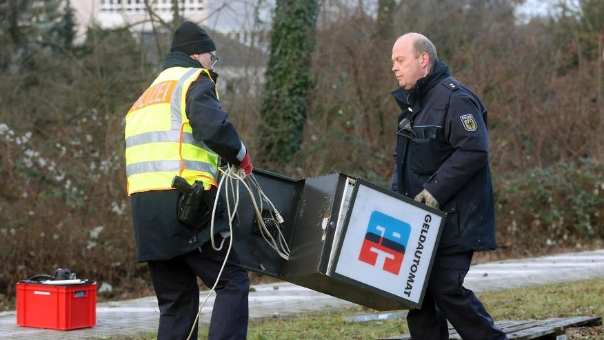Police officers gather the remains of a cash machine at the railway station in Dinslaken, Germany, Thursday Jan. 12, 2017.  A freight train has partly derailed in Germany after hitting a stolen cash machine that had been left on the track. Police said no one was hurt in the incident before dawn Thursday in Dinslaken in western Germany. (Roland Weihrauch/dpa via AP)