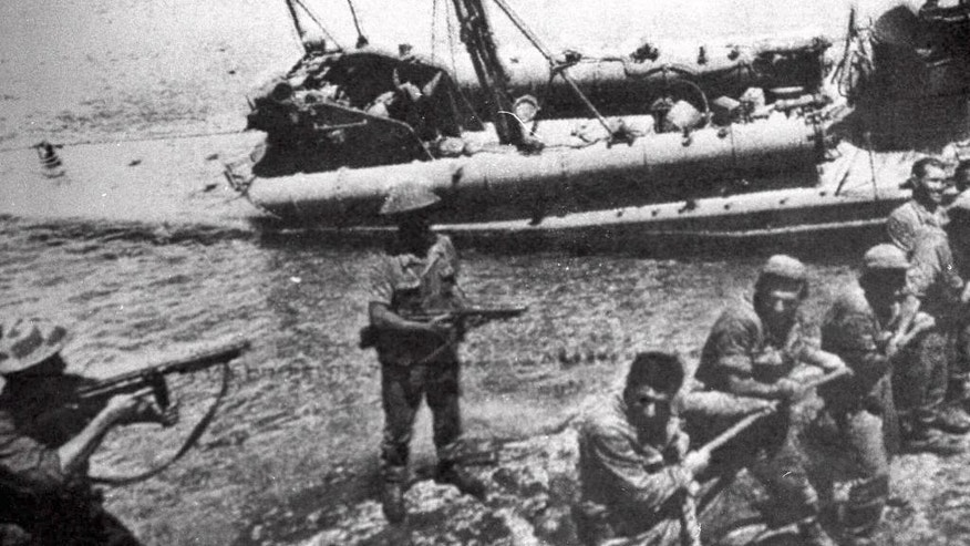 FILE- In this July 20 1974, file photo Turkish troops pull ashore a Greek Cypriot torpedo boat damaged during fighting in Kyrenia on the day Turkey invaded and occupied the northern third of Cyprus. Talks on reunifying the small Mediterranean island nation of Cyprus are now at a critical juncture with top officials from Britain, Greece, and Turkey joining the talks in Geneva Thursday, Jan. 12 , to tackle the thorny issue of security. (AP Photo, File)