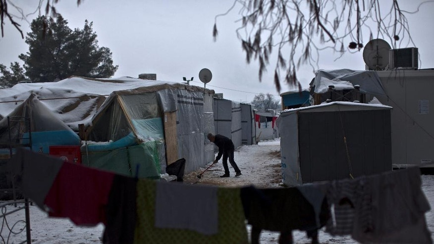 "A Syrian refugee man clears the snow around his shelter at the refugee camp of Ritsona about 86 kilometers (53 miles) north of Athens, Wednesday, Jan. 11, 2017. The European Commission said conditions for refugees on islands and other camps where they are housed in tents despite severe cold weather, is ""untenable."" (AP Photo/Muhammed Muheisen)"