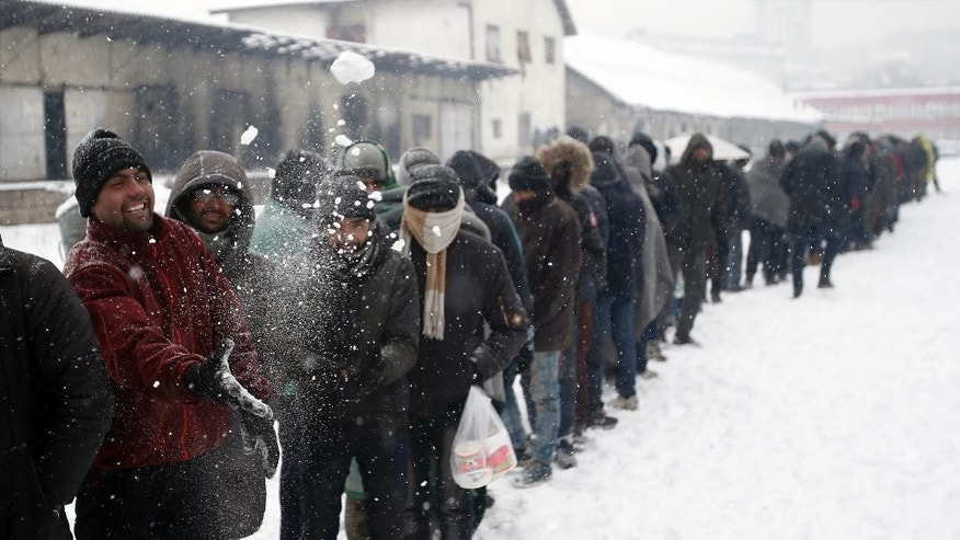 Migrants queue for food in front of an abandoned warehouse in Belgrade, Serbia, Wednesday, Jan. 11, 2017. Hundreds of migrants are sleeping rough in parks and make-shift shelters in the Serbian capital in freezing temperatures waiting for a chance to move forward toward the European Union. (AP Photo/Darko Vojinovic)