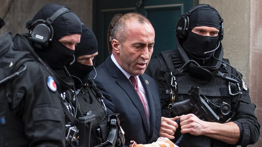 Former prime minister of Kosovo Ramush Haradinaj, center, leaves the court escorted by hooded police officers in Colmar, eastern France, Thursday, Jan. 12, 2017. A French court has ordered the release of a jailed former prime minister of Kosovo pending a decision on whether to extradite him to Serbia, where he's wanted on war crimes charges. (AP Photo/Jean-Francois Badias)