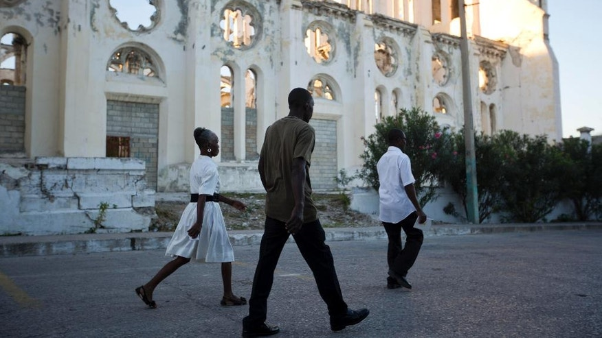 Residents walk to attend a mass, as they past the ruins of the National Cathedral during the 7th anniversary of the January 2010 earthquake in Port-au-Prince, Haiti. Thursday, Jan. 12, 2017. The earthquake caused major damage in Port-au-Prince, Jacmel and other settlements in the region killing tens of thousands. ( AP Photo/Dieu Nalio Chery)