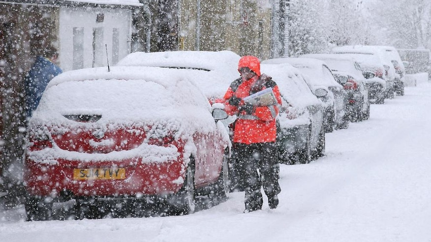 A postman struggles in the snow while making deliveries in Stirling, Scotland, Thursday, Jan. 12, 2017. Snow showers and strong winds are expected across Scotland, Northern Ireland, Wales and the north of England on Thursday. (Andrew Milligan/PA via AP)