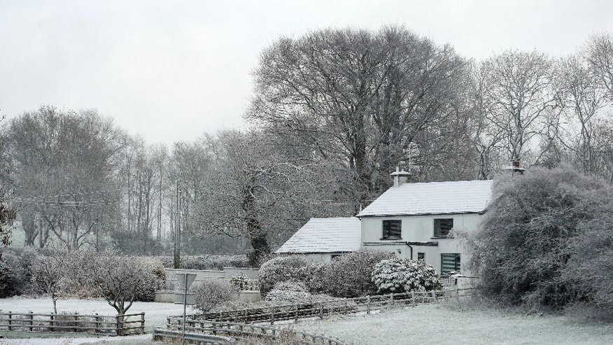 A snow covered house is seen in County Antrim, Northern Ireland, Thursday, Jan. 12, 2017. Snow showers and strong winds are expected across Scotland, Northern Ireland, Wales and the north of England on Thursday. (Niall Carson/PA via AP)