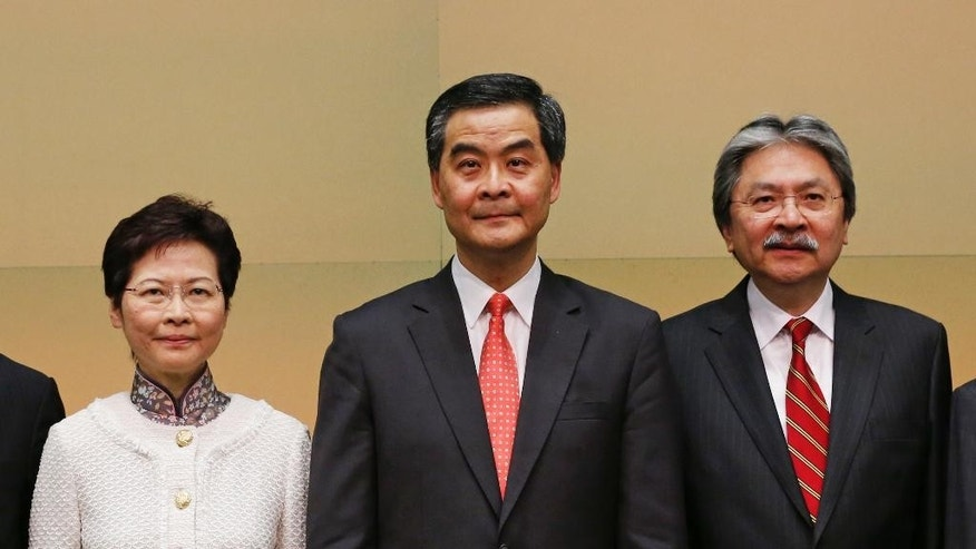 In this Thursday, June 28, 2012, photo, from left; Hong Kong Chief Secretary for Administration Carrie Lam, Chief Executive Leung Chun-ying and Financial Secretary John Tsang, line up during the news conference in Hong Kong. Lam, the No. 2 government official who announced her resignation, and Hong Kong's Financial Secretary John Tsang, who resigned last month, are widely expected to mount leadership bids for the job of Hong Kong's top leader after current Chief Executive Leung Chun-ying said he would not go for a second term. (AP Photo/Kin Cheung)