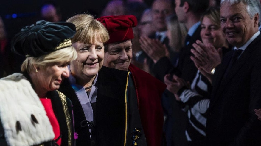 German Chancellor Angela Merkel, second left, walks in between the Rector of the University of Leuven Rik Torfs, center, and the Rector of the University of Ghent Anne De Paepe, left, as she arrives to receive an honorary doctorate during an academic ceremony in Brussels on Thursday Jan. 12, 2017. Merkel received the honorary doctorate for her diplomatic and political efforts to develop the political strength of Europe, and to defend the values that allow Europe to find unity in diversity. (AP Photo/Geert Vanden Wijngaert)