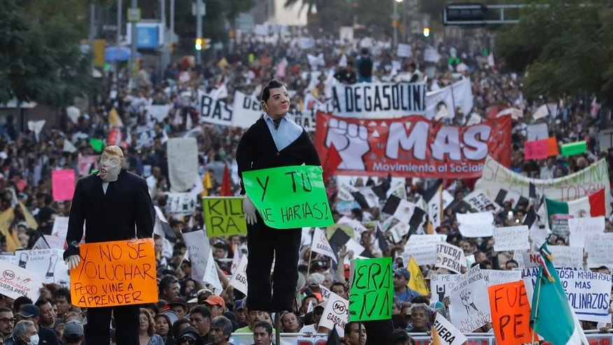 "People carry effigies of Mexican President Enrique Pena Nieto and U.S. President-elect Donald Trump, as thousands marched in anger against the government following a 20 percent rise in gas prices, in Mexico City, Monday, Jan. 9, 2017. The effigy of Pena Nieto, holding a sign reading in Spanish ""And what would you do?"" and that of Trump, marked with ""I don't know how to struggle, but I came here to learn,"" were later burned. (AP Photo/Rebecca Blackwell)"