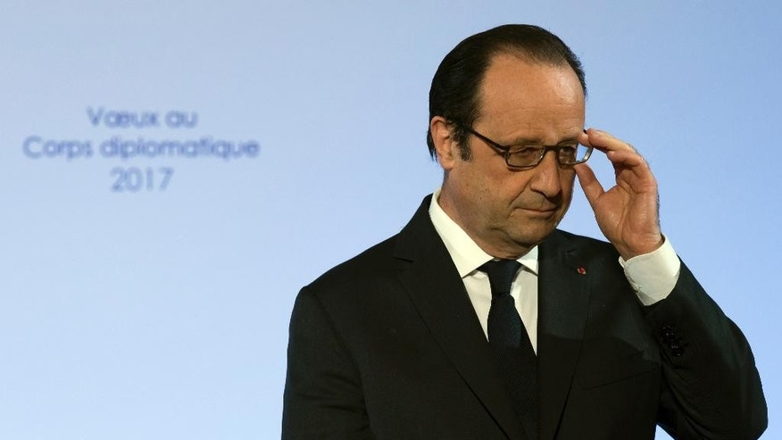 French president Francois Hollande adjusts his glasses as he delivers his new year address to diplomats, at the Elysee Palace in Paris,Thursday, Jan. 12 2017. Hollande says Sunday's Mideast peace conference in Paris aims at ensuring the support of the international community for the two-state solution as a reference for future direct negotiations. (Ian Langsdon, Pool via AP)