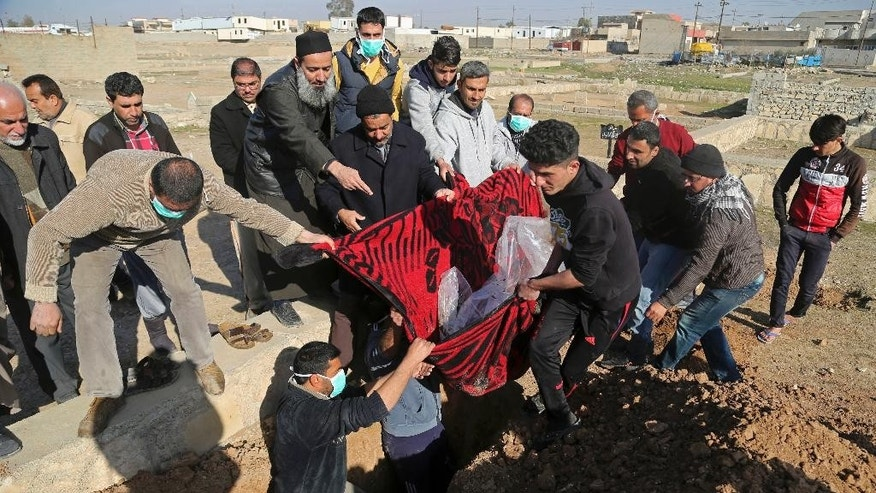 Mourners bury Musaap Yaser Hazem, 17, who died in a Islamic State mortar attack, in Mosul, Iraq, Wednesday, Jan. 11, 2017. Hazem's father said his son was killed during a Islamic State mortar attack in early December 2016, and had to be buried in the neighborhood because of the poor security situation. On Wednesday, approximately a month after he died, the security situation had improved and the family were finally able to give Hazem a proper burial in the Mosul cemetery. (AP Photo/Khalid Mohammed)