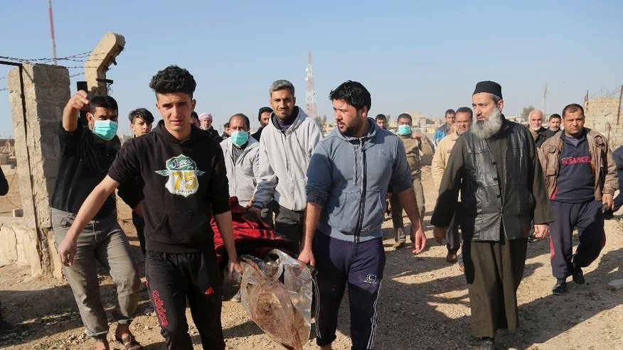 Mourners take the body of Musaap Yaser Hazem, 17, who died in a Islamic State mortar attack, to be buried, in Mosul, Iraq, Wednesday, Jan. 11, 2017. Hazem's father said his son was killed during a Islamic State mortar attack in early December 2016, and had to be buried in the neighborhood because of the poor security situation. On Wednesday, approximately a month after he died, the security situation had improved and the family were finally able to give Hazem a proper burial in the Mosul cemetery. (AP Photo/Khalid Mohammed)