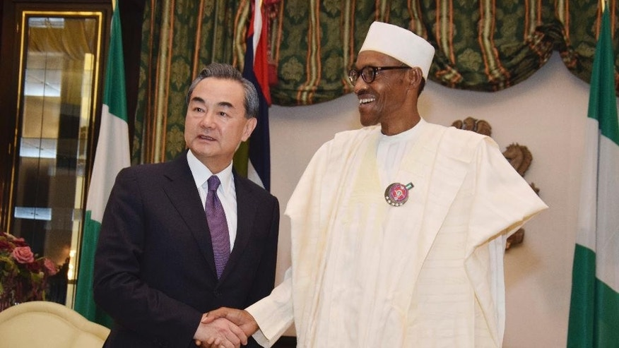 FILE- In this Wednesday, Jan. 11, 2017 file photo, Chinese Foreign Minister, Wang Yi, left, is welcomed by Nigeria President Muhammadu Buhari, at the Presidential Villa in Abuja, Nigeria. Taiwan is protesting against Nigeria's demand that it relocate its trade office, following a visit by China's foreign minister and a promise of $40 billion in investment. (AP Photo/ Azeez Akunleyan File)