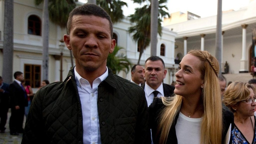 FILE - In this Jan. 11, 2016, file photo, opposition activist Gilbert Caro, left, and LilianTintori, wife of opposition jailed leader Leopoldo Lopez, arrive at the National Assembly in Caracas, Venezuela. Caro was detained Wednesday, Jan. 11, 2017, at a highway toll station after police said they found a gun and explosives in his car. His Popular Will party said the weapons were planted to frame him. (AP Photo/Fernando Llano, File)