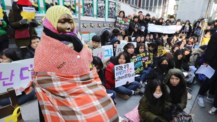 "FILE - IN this Wednesday, Jan. 11, 2017, file photo, students gather near a ""comfort-woman"" statue during a rally in front of the Japanese Embassy in Seoul, South Korea.'Comfort women"" were present wherever the Japanese Imperial Army invaded and occupied in Asia from the early 1930s through the end of World War II. That aspect of wartime history was kept quiet until the early 1990s, when a South Korean woman came forward, joined by some others, seeking Japanese help and accountability. (AP Photo/Lee Jin-man, File)"
