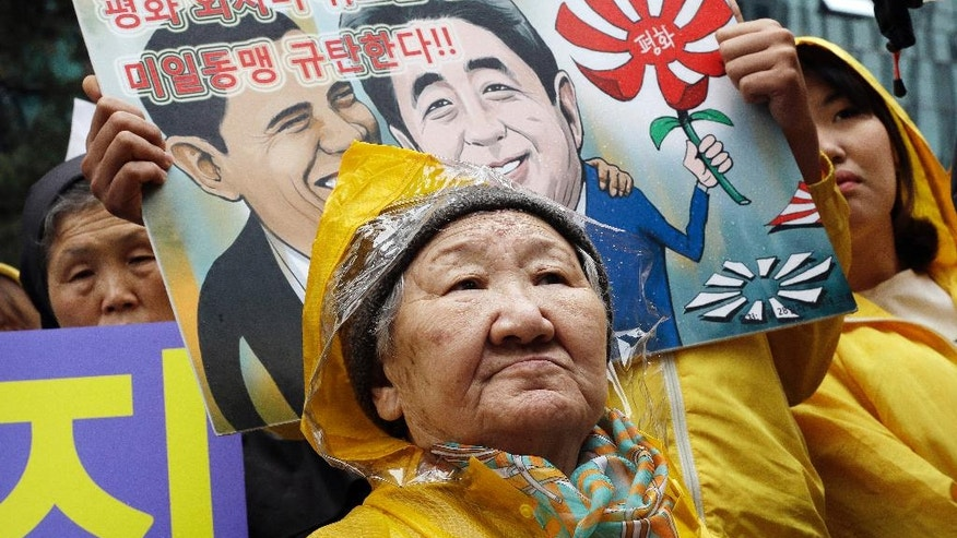 "FILE - In this Wednesday, April, 29, 2015, file photo, a former comfort woman Kil Un-ock, who was forced to serve for the Japanese troops as a sexual slave during World War II, attends a rally against a visit by Japanese Prime Minster Shinzo Abe to the United States, in front of the Japanese Embassy in Seoul, South Korea. 'Comfort women"" were present wherever the Japanese Imperial Army invaded and occupied in Asia from the early 1930s through the end of World War II. That aspect of wartime history was kept quiet until the early 1990s, when a South Korean woman came forward, joined by some others, seeking Japanese help and accountability. The letters at a card read "" Oppose the alliance between U.S. and Japan."" (AP Photo/Ahn Young-joon, File)"