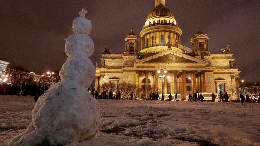 A snowman stands in front of the St. Isaac's Cathedral in St.Petersburg, Russia, Friday, Jan. 13, 2017. In the latest scandal involving the powerful Russian Orthodox Church, authorities in St. Petersburg on Thursday defended a controversial decision to give a city landmark cathedral to the church. (AP Photo/Dmitri Lovetsky)