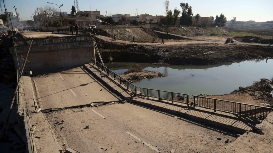 Jan. 12, 2017: People inspect a bridge destroyed by Islamic State militants in a neighborhood recently liberated from Islamic State on the eastern side of Mosul, Iraq.