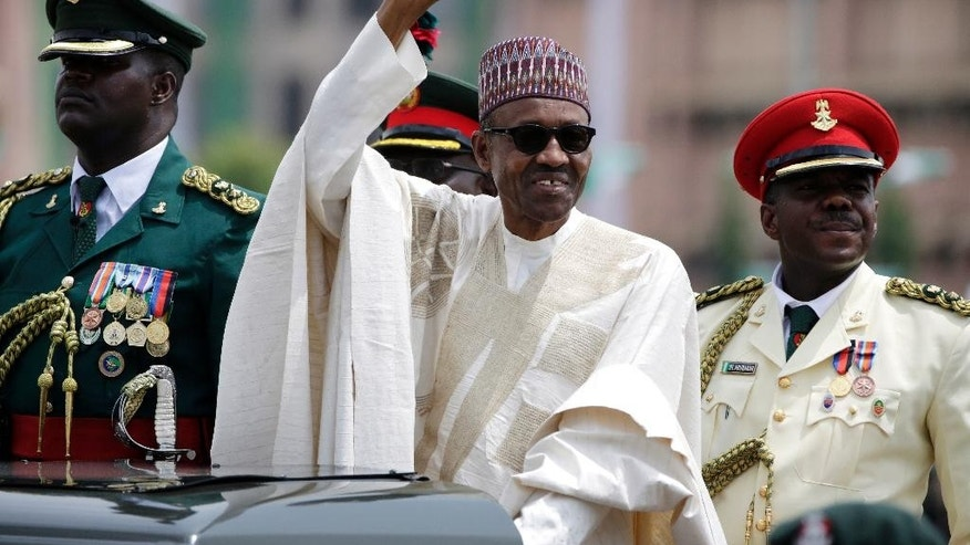 FILE - In this May 29, 2015, file photo, Nigerian President Muhammadu Buhari salutes his supporters during his inauguration in Abuja, Nigeria. Buhari is leading a regional delegation to Gambia in a last-ditch attempt to persuade its longtime leader to step down and allow his rival's inauguration next week. Buhari has been authorized to offer Gambian President Yahya Jammeh asylum, if necessary, during Friday, Jan. 13, 2017, visit. (AP Photo/Sunday Alamba, File)
