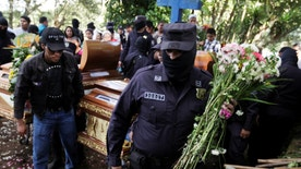 Salvadoran police officers participate in the funeral ceremony for their colleague Lorenzo Rojas Herrera and his son Marvin in Quezaltepeque, El Salvador, November 18, 2016. Sergeant Lorenzo Rojas and his son were killed by suspected members of the Mara Salvatrucha gang, according to the police. REUTERS/Jose Cabezas - RTSSBU5