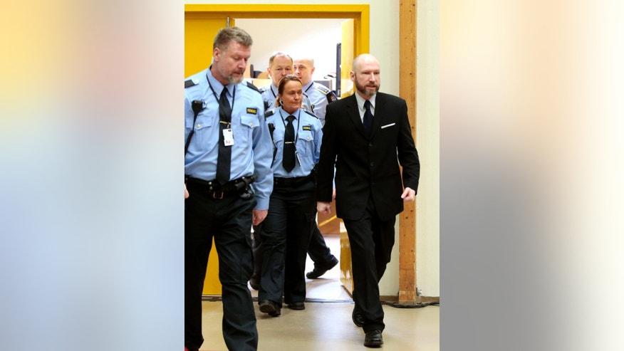 Anders Behring Breivik, right, escorted by police officers, enters a courtroom on the fourth day of the appeal case in Borgarting Court of Appeal at Telemark prison in Skien, Norway, Friday, Jan. 13, 2017. Norwegian mass murderer Breivik told a panel of judges Thursday that his solitary confinement in prison had deeply damaged him and made him even more radical in his neo-Nazi beliefs. (Lise Aaserud/NTB scanpix via AP)