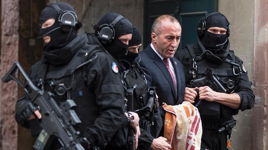 Former prime minister of Kosovo Ramush Haradinaj, second right, leaves the court escorted by hooded police officers in Colmar, eastern France, Thursday, Jan. 12, 2017. A French court has ordered the release of a jailed former prime minister of Kosovo pending a decision on whether to extradite him to Serbia, where he's wanted on war crimes charges. (AP Photo/Jean-Francois Badias)