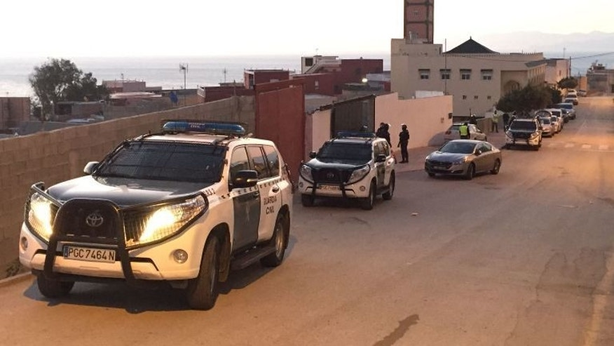 In this photo released by the Spanish Guardia Civil on Friday, Jan. 13, 2017, Spanish Guardia Civil officers stand guard in front of a house during a terrorist operation in Ceuta, Spain. Spanish police on Friday arrested two people for suspected terrorism offenses linked to the Islamic State group, the Interior Ministry said. The ministry said the two arrested Friday in Spain's North African enclave city of Ceuta had undergone a long process of radicalization and formed part of a group that was advancing toward carrying out terror activities. (Spanish Interior Ministry via AP)