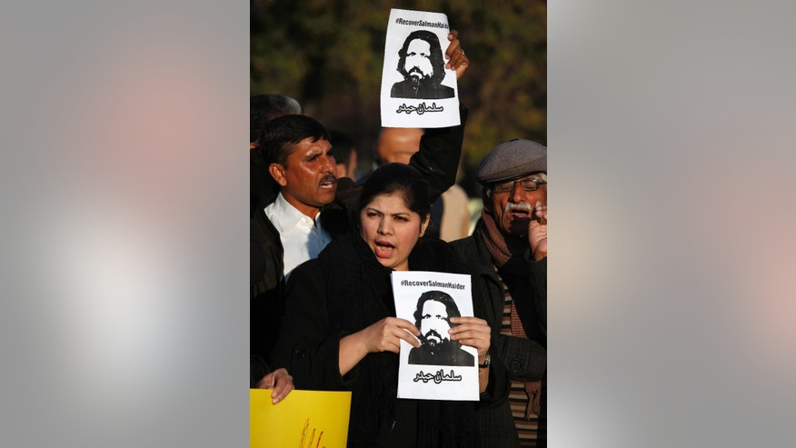 Pakistan's civil society members hold portraits of missing university professor Salman Haider while they chant slogans during a demonstration to condemn the missing human rights activists, in Islamabad, Pakistan, Tuesday, Jan. 10, 2017. International and local rights groups on Tuesday urged the Pakistani government to investigate the abductions last week of four anti-Taliban activists — disappearances that critics claim reflect a crackdown on secular dissent. (AP Photo/Anjum Naveed)