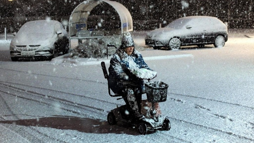 A woman makes her way through the snow on a mobility scooter in Filey on the North east coast of England Friday Jan. 13, 2017, as Scotland and the North of England were covered in a blanket of snow. (John Giles, PA via AP)