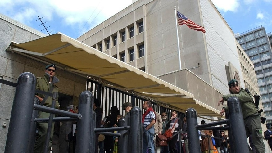 FILE - In this March 17, 2003 file photo, an Israeli border policemen guards the U.S. Embassy in Tel Aviv as Israelis line up for U.S. visas. The Palestinians are ringing alarm bells over Donald Trump's stated intention to relocate the U.S. Embassy in Israel to contested Jerusalem, fearing quick action once he takes office as U.S. president next week. They said an embassy move would kill any hopes for negotiating an Israeli-Palestinian border deal and rile the region by undercutting Muslim and Christian claims to the holy city. (AP Photo/Eitan Hess-Ashkenazi, File)