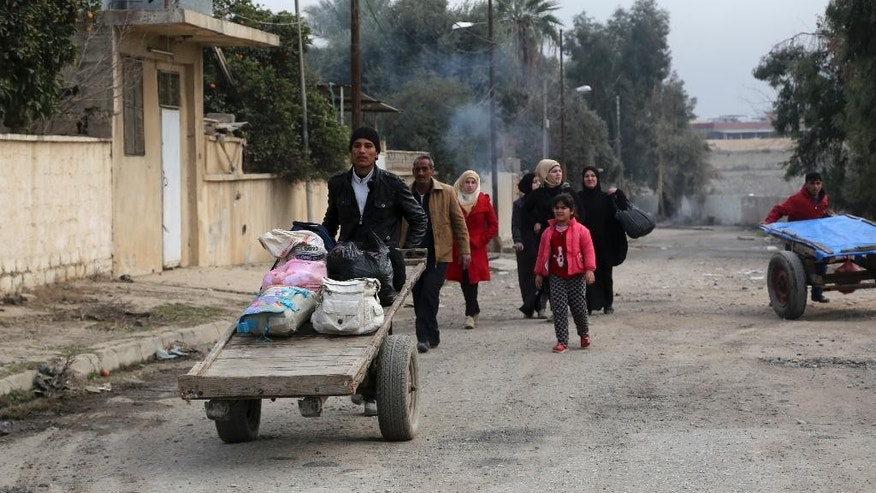 Civilians return to their neighborhood recently liberated from Islamic State militants in the eastern side of Mosul, Iraq, Friday, Jan. 13, 2017.  Iraqi special forces entered Mosul University on Friday in their latest advance along the eastern front as they battle Islamic State militants for control of the city, according to senior Iraqi officers. (AP Photo/ Khalid Mohammed)