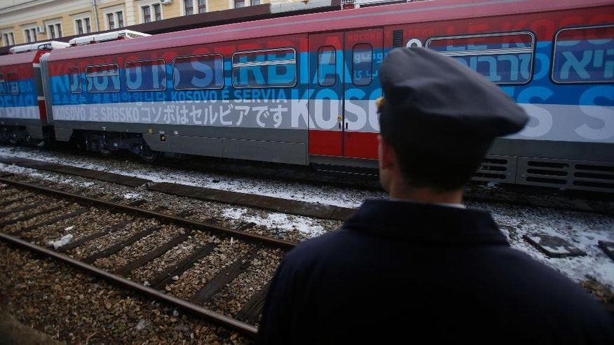 "A railroad worker stands by the first train decorated with letters that read ""Kosovo is Serbian"" written in twenty languages departing from the Belgrade to Mitrovica, Kosovo at Belgrade's railway station, Serbia, Saturday, Jan. 14, 2017. Serbia has launched a railway link to Serb-dominated northern Kosovo despite protests from authorities in Pristina who described the move as a provocation and an aggressive violation of Kosovo's sovereignty. (AP Photo/Darko Vojinovic)"