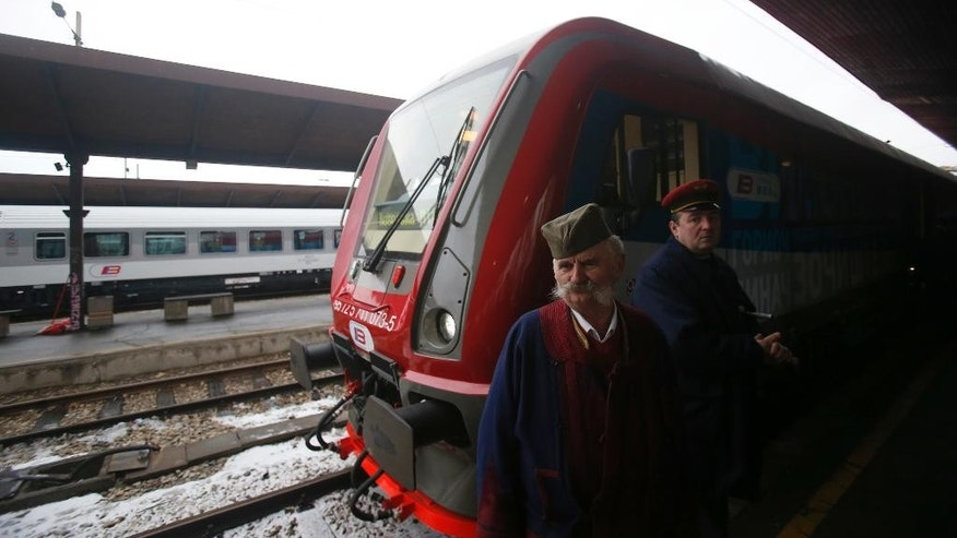 "A man dressed in Serbian national costume passes by a train decorated with ""Kosovo is Serbian"" inscribed in twenty world languages before it departs from Belgrade to Mitrovica, Kosovo at Belgrade's railway station, Serbia, Saturday, Jan. 14, 2017. Serbia has launched a railway link to Serb-dominated northern Kosovo despite protests from authorities in Pristina who described the move as a provocation and an aggressive violation of Kosovo's sovereignty. (AP Photo/Darko Vojinovic)"