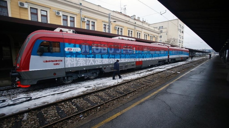 "A railroad worker walks by the first train decorated with letters that read ""Kosovo is Serbian"" written in twenty languages departing from the Belgrade to Mitrovica, Kosovo at Belgrade's railway station, Serbia, Saturday, Jan. 14, 2017. Serbia has launched a railway link to Serb-dominated northern Kosovo despite protests from authorities in Pristina who described the move as a provocation and an aggressive violation of Kosovo's sovereignty. (AP Photo/Darko Vojinovic)"
