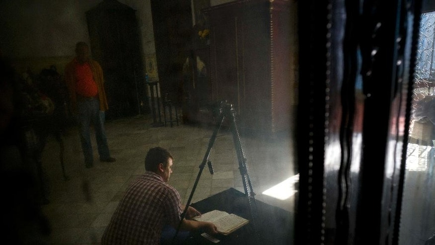 This Jan. 12, 2017 photo shows U.S. history professor David Lafevor taking photos of a colonial-era registries inside Espiritu Santo Church in Old Havana, Cuba. While digitalizing documents in the town of Colon, a slave trading post in colonial days, Lafavor discovered the existence of a nearby town founded by former American slaves who had fled the mainland from what had been Spanish ruled Florida. (AP Photo/Ramon Espinosa)